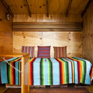 Inside is a fold down single bed and a desk made from cupboard doors